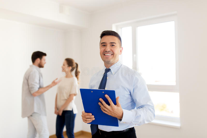 Realtor with clipboard and couple at new home. Real estate, mortgage and people concept - happy smiling realtor with clipboard and couple at new home stock photo