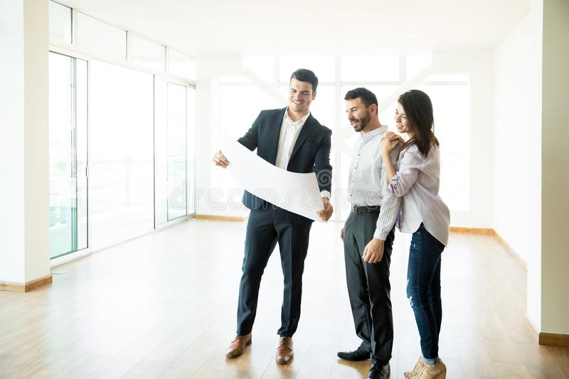 Realtor Discussing Apartment Layout With Couple In Empty Room royalty free stock images