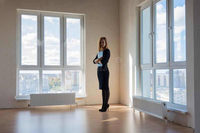 Realtor expects buyers in a large room with huge windows. Realtor expects buyers in a large room with huge  windows stock photo