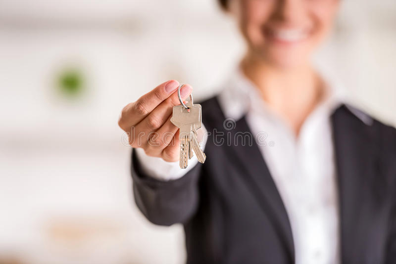 Realtor. Is giving the keys to an apartment to clients. Focus on the keys