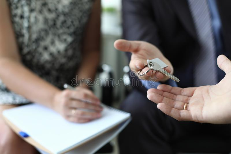 Realtor is handing over key of new apartment royalty free stock photography