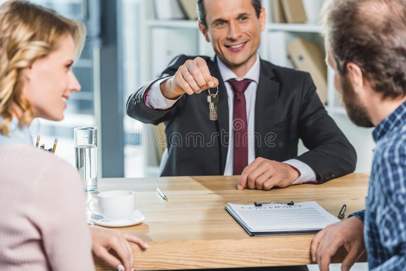 Realtor with keys in hand. Selective focus of smiling realtor giving keys from new home to couple in office royalty free stock photography