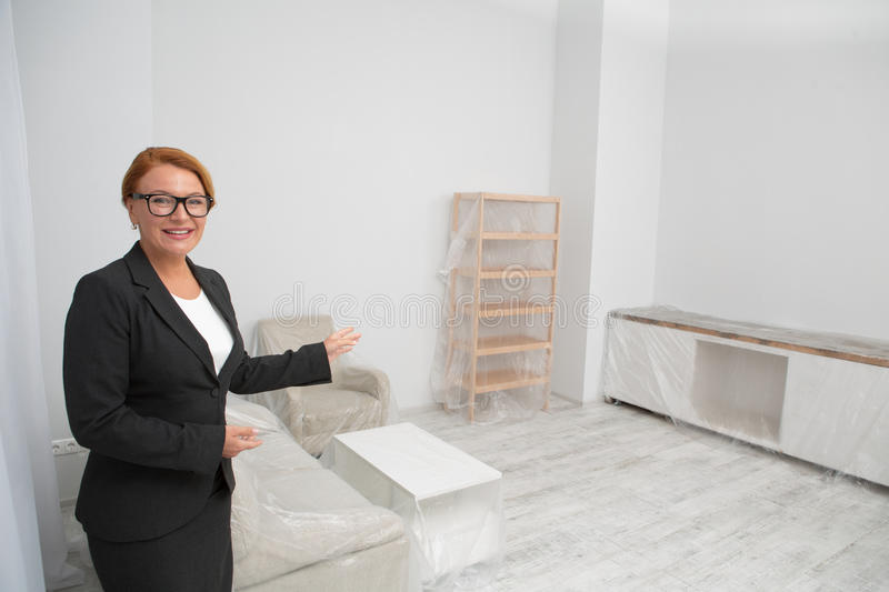 Realtor in living room proposing to view an apartment. Real estate agent showing an apartment with white walls and furniture covered with foil stock images