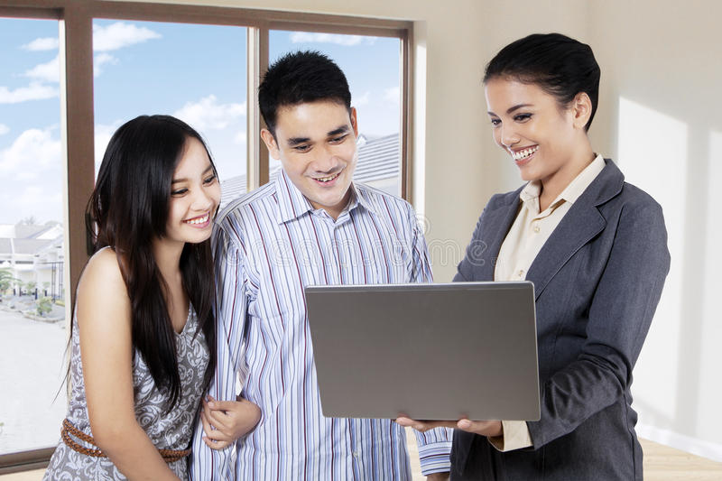 Realtor presenting new house to couple. Female realtor showing new house to couple with a laptop computer inside the new house royalty free stock images