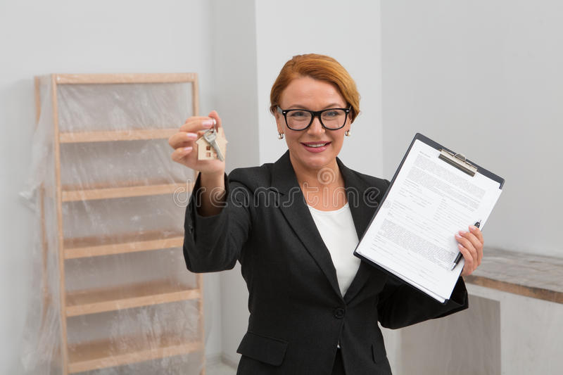 Realtor proposing to sign an agreement for apartment rent, camera focused on face. Woman realtor stnading in the room with keys and agreement in her hands royalty free stock photography