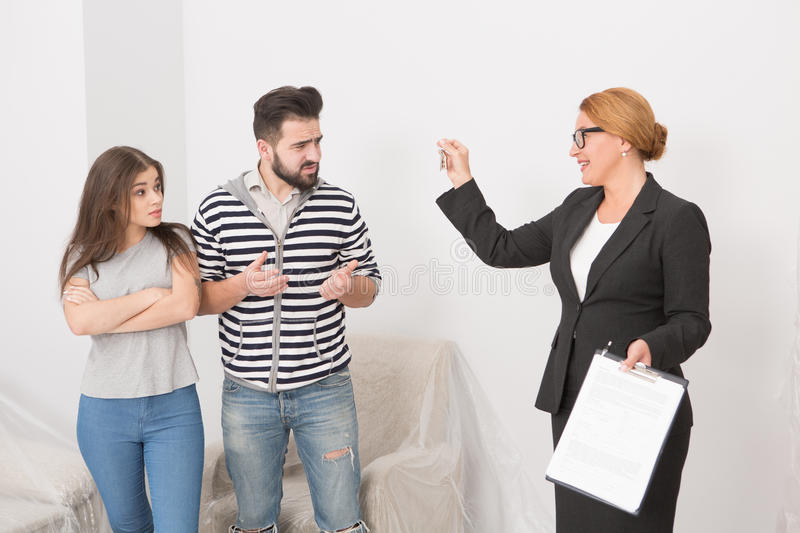 Realtor proposing to sign a cotract to man and woman. wha are not agree. Realtor proposing to sign a cotract to men and woman. wha are not agree. Happy estate royalty free stock photos