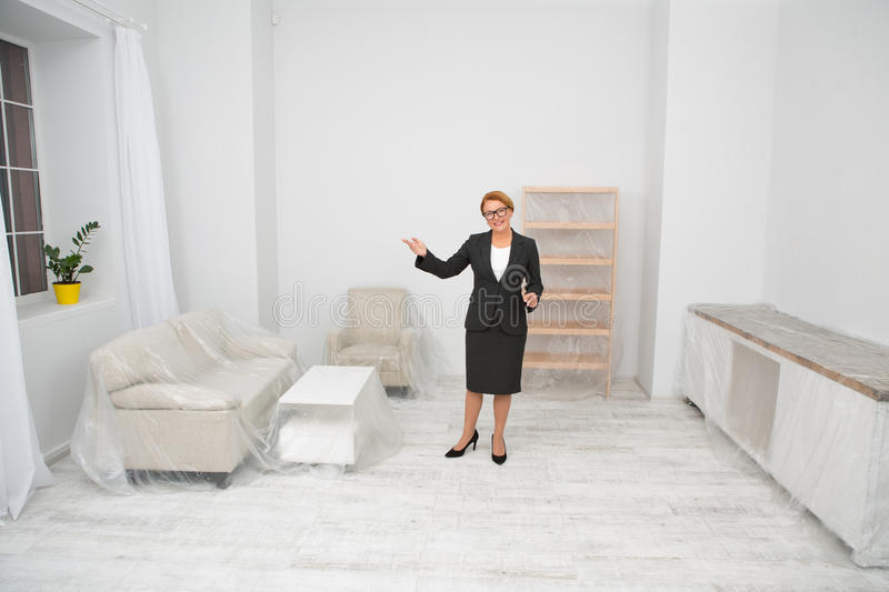Realtor proposing to visit flat-apartment. Mid aged woman standing in the middle of white living room with furniture covered with foil stock photography