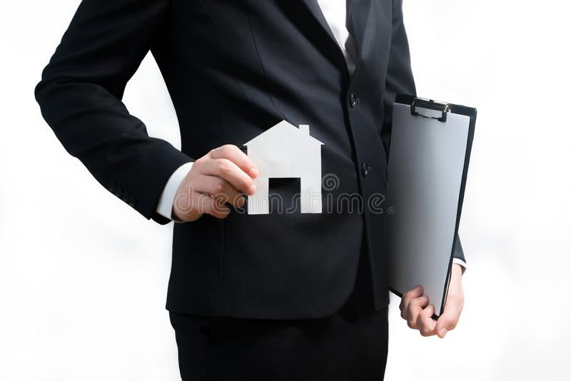 Realtor, real estate agent holding tablet and paper model of a h. Ouse. Getting access to home. Investment and buying property concept royalty free stock image