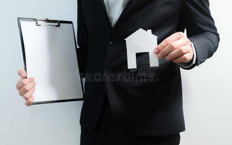 Realtor, real estate agent holding tablet and paper model of a house. Getting access to home. Investment and buying property stock photo