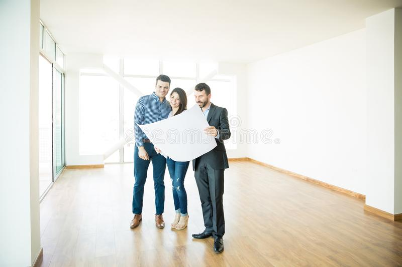 Realtor Showing Architectural Plan To Couple In New House. Mid adult realtor showing architectural plan to couple in new house stock photography