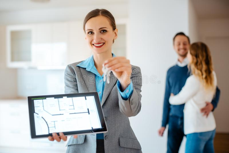 Realtor showing home keys and floorplan of apartment. To buy or rent stock image
