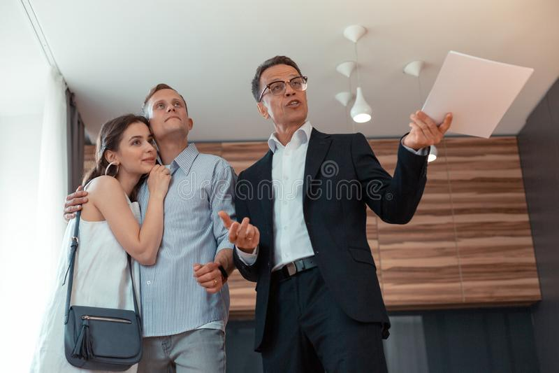 Realtor wearing glasses speaking to clients telling about the house stock photo