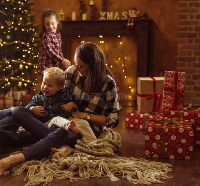 realxing在一个冬天晚上的一个快乐的家庭的画象 图库摄影