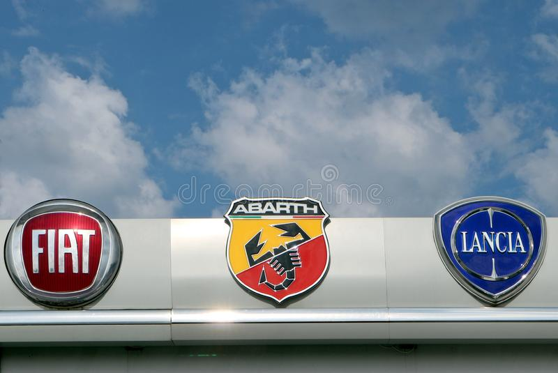 Fiat, Abarth and Lancia logos in the dealership of the area, against a blue sky  with clouds. They are all part of the Fiat Group royalty free stock photos