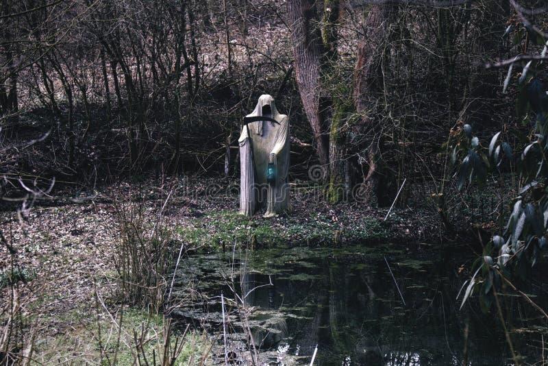 Reaper blanc de la mort avec la faux fantasmagorique et la lampe à un petit étang photographie stock