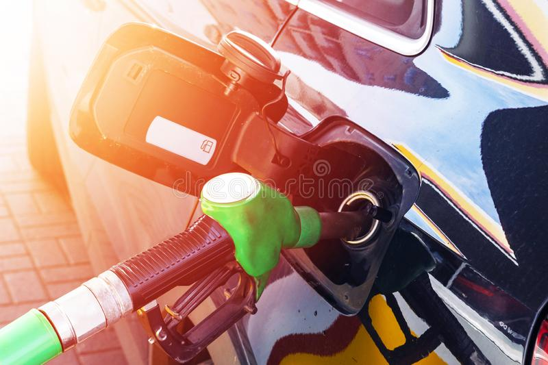 Reaprovisionamiento del coche de combustible en un surtidor de gasolina de la gasolinera Aceite que rellena y de bombeo de la man imagen de archivo