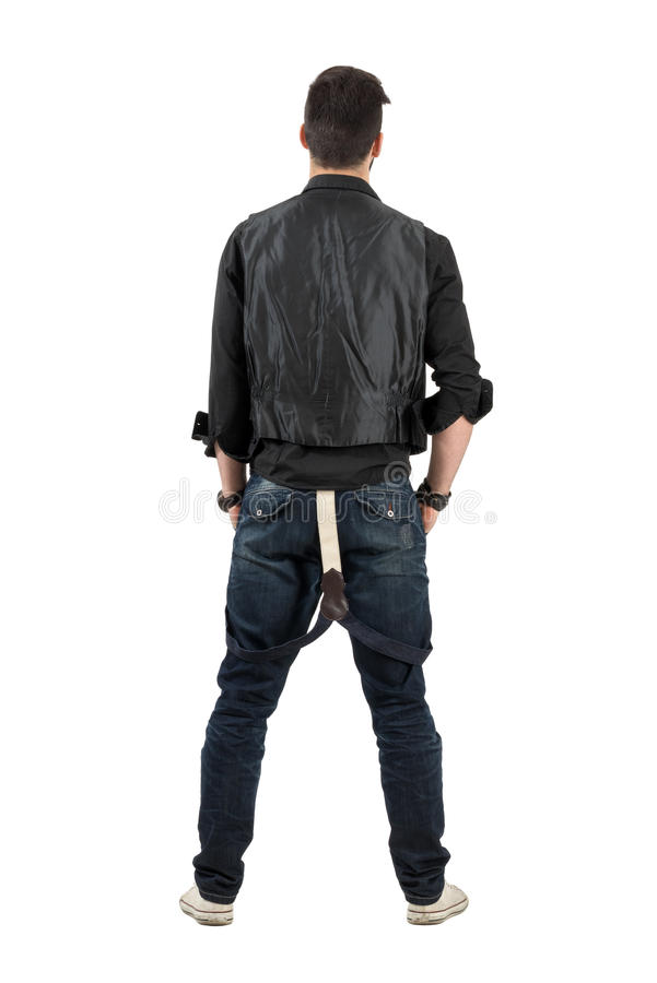 Rear backside view of young stylish man looking at blank wall stock image