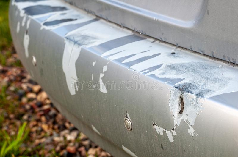 Rear bumper sedan damaged in an accident on the road. Close-up of the rear bumper of a sedan to get damage from an accident on the road. Shabby and scratched royalty free stock images