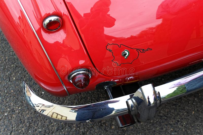 Rear car fender of an oldtimer. Photo of the left rear fender and bumper corner of an Austin-Healey oldtimer with taillights and a Nordschleife sticker stock image