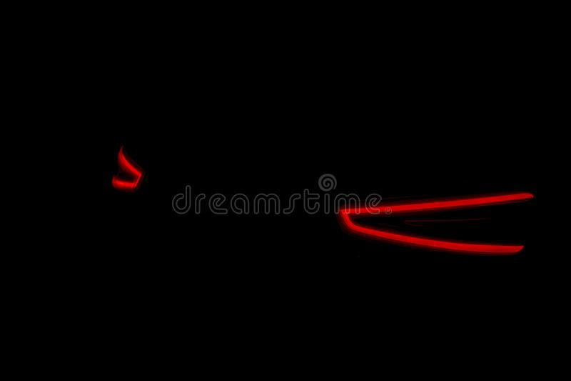 Rear car lights on a black background. Cars light trails. Night city road with traffic headlight. Light up road by vehicle. Car li royalty free stock photos