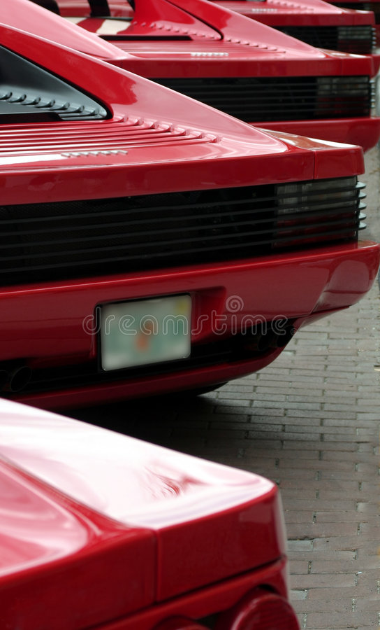Rear ends of red exotic sports cars in a row stock photo