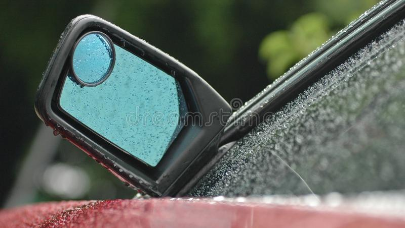 Rear mirror of a brand new red car in rainy day with droplet. And the left window has blue reflection stock photos