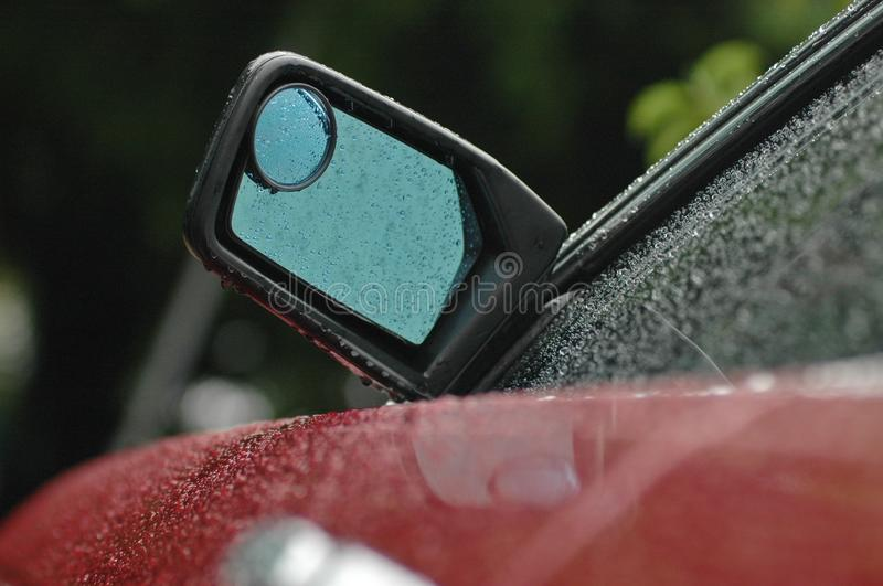Rear mirror of a brand new red car in rainy day with droplet. Water on a red car in rainy season royalty free stock photo