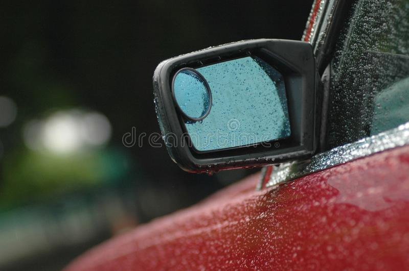 Rear mirror of a brand new red car in rainy day with droplet. Rear mirror of a brand new red car in rainy day with water droplet in the afternoon royalty free stock images