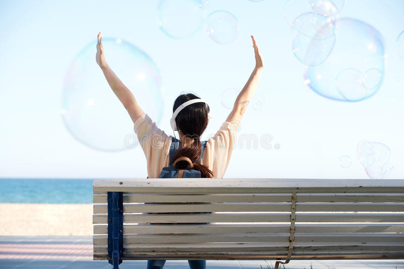 Rear of woman with arms outstretched by sea with bubbles royalty free stock images