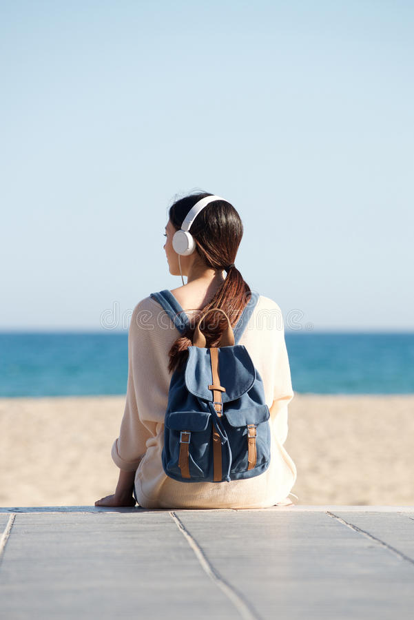 Woman sitting by sea with headphones and backpack stock photography