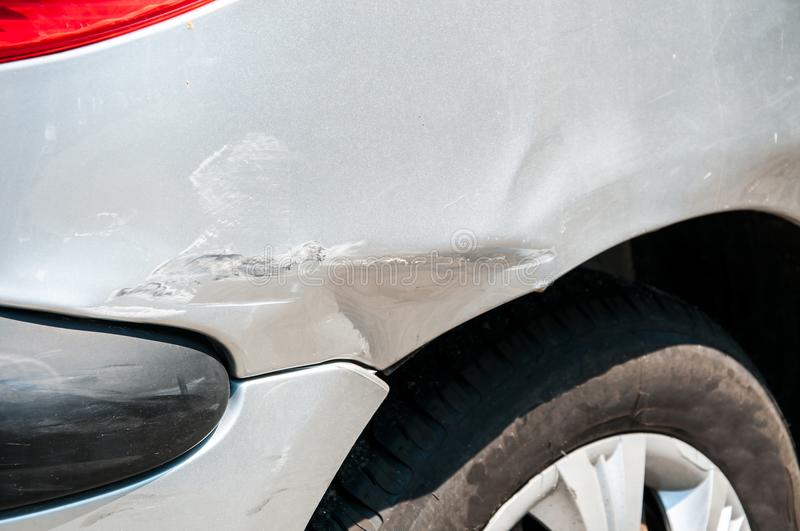Rear side of broken and damaged silver car wreck in crash accident with scratched paint in collision close up stock image