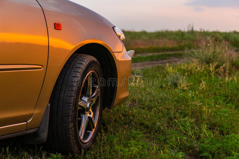 Rear-side view of a luxury car on sunset. Road, auto, automobile, vehicle, new, detail, travel, horizon, vacation, reflection, transportation, shine, mirror royalty free stock photo