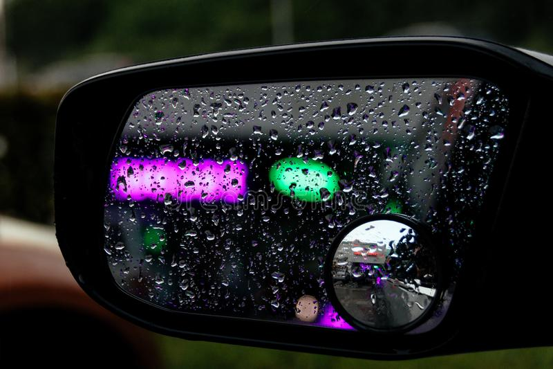 Rear side-view mirror covered in water droplets after he rain, Green and pink neon reflected lights. stock photography