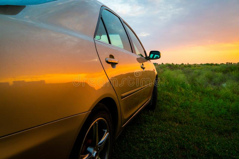 Rear-side view of a unidentified luxury car on sunset. Road, auto, automobile, vehicle, new, detail, travel, horizon, vacation, reflection, transportation stock photo