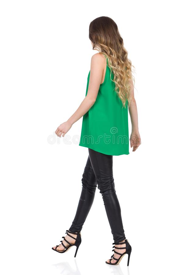 Rear Side View of Walking Woman In Leather Trousers And High Heels stock photography