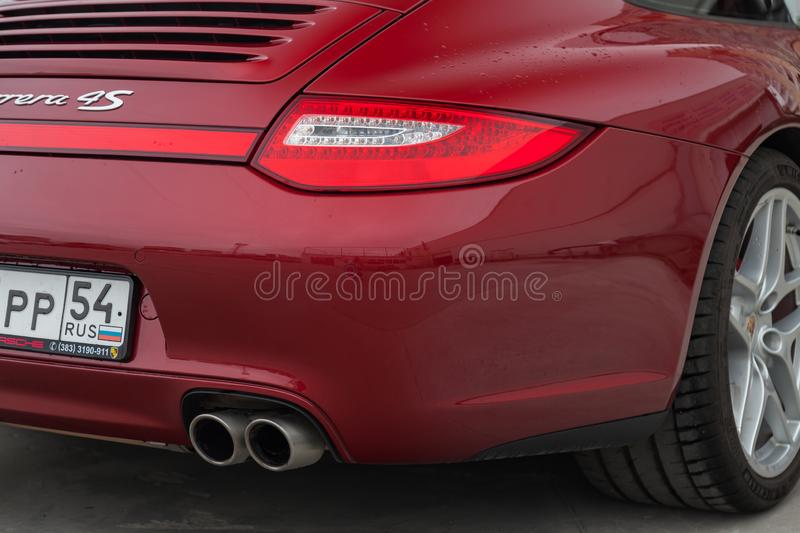 Rear taillamp and exhaust view of car Porsche 911 Carrera 4s with dark gray interior in excellent condition in a parking against. Novosibirsk, Russia - 07.17 stock image