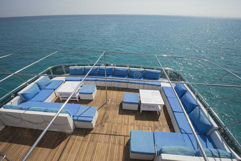 Rear Teak Deck Of A Large Luxury Motor Yacht With Chairs Sofa Table And  Tropical Sea View Background