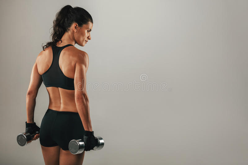 Rear three quarter view of female bodybuilder. Rear three quarter view of beautiful female bodybuilder with pony tail and black outfit stock image