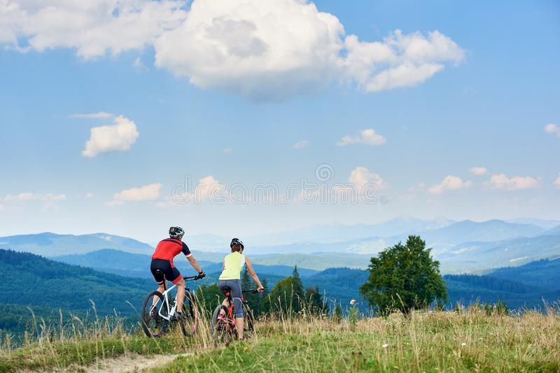 Rear view of active couple bikers in professional sportswear riding cross country bicycles down stock photos