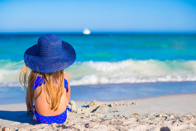 Rear view of adorable little girl in big blue stock image