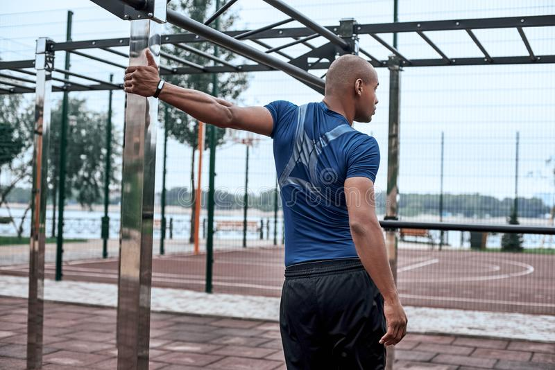 Rear view of an african sportive man who is stretching hands. Rear view of an african fitness man stretching hands on a quay background at the park royalty free stock image