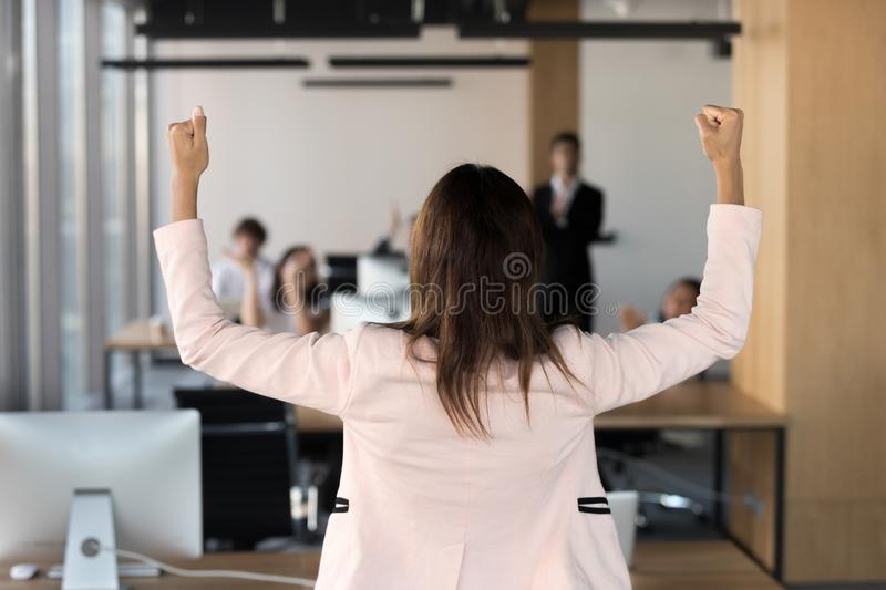 Rear view african team leader raising hands celebrating victory royalty free stock photo