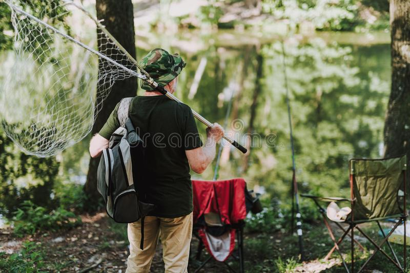 Rear view of an aged man standing with fishing equipment stock photography