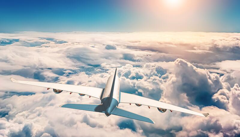Rear view of airplane or airliner flying over sea of clouds and sun shining in the background. Travel, transportation or transport royalty free stock photography
