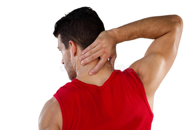 Rear view of American football player suffering from neck pain. While standing against white background stock photography