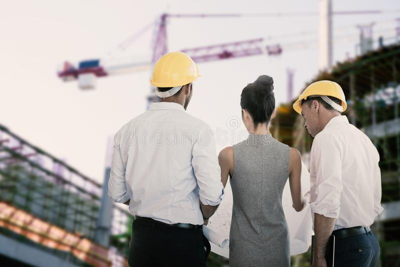 Composite image of rear view of architects discussing over blueprint royalty free stock image