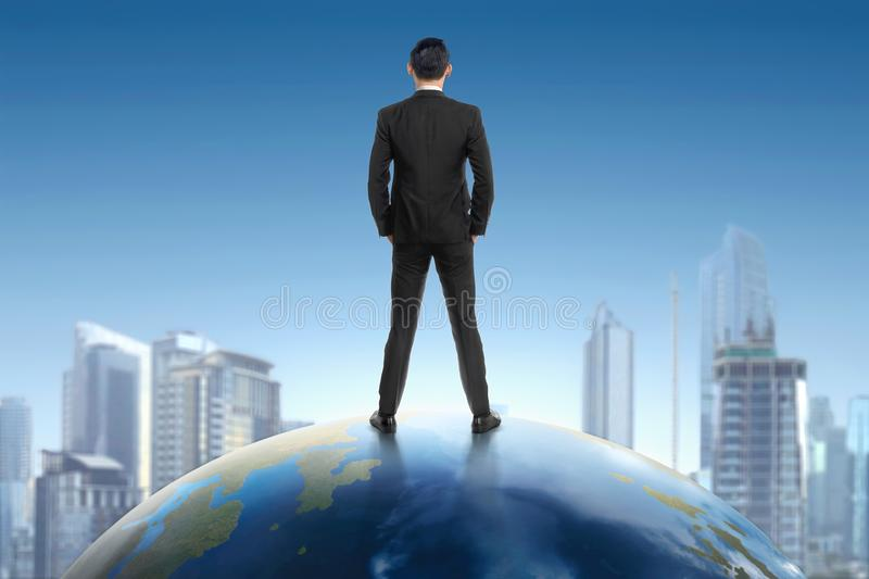 Rear view of asian businessman standing on earth and looking at. Cityscape view with blue sky background royalty free stock photos