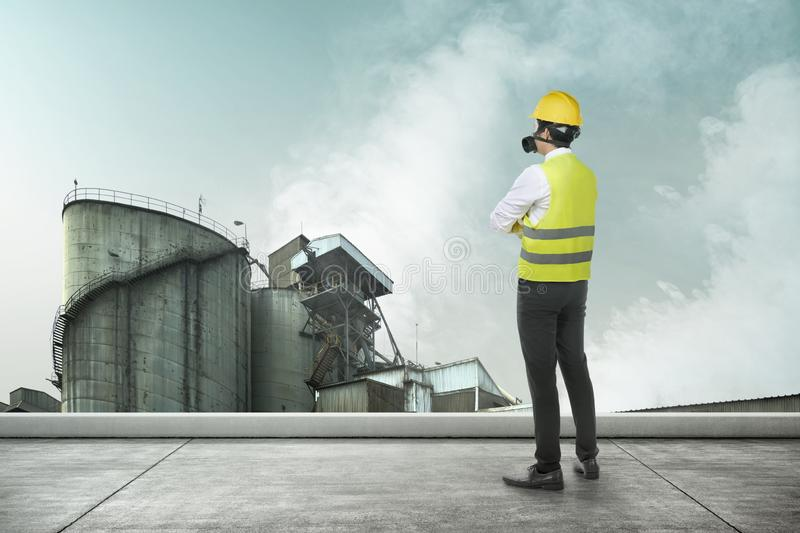 Rear view of Asian construction engineer man with a protective mask looking at smoke and air pollution stock photography
