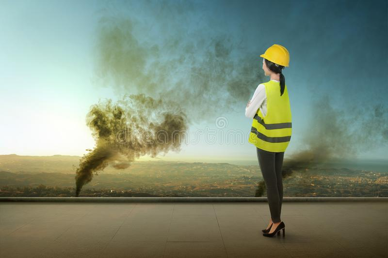 Rear view of Asian construction engineer woman looking at dark smoke and air pollution from forest fires royalty free stock images