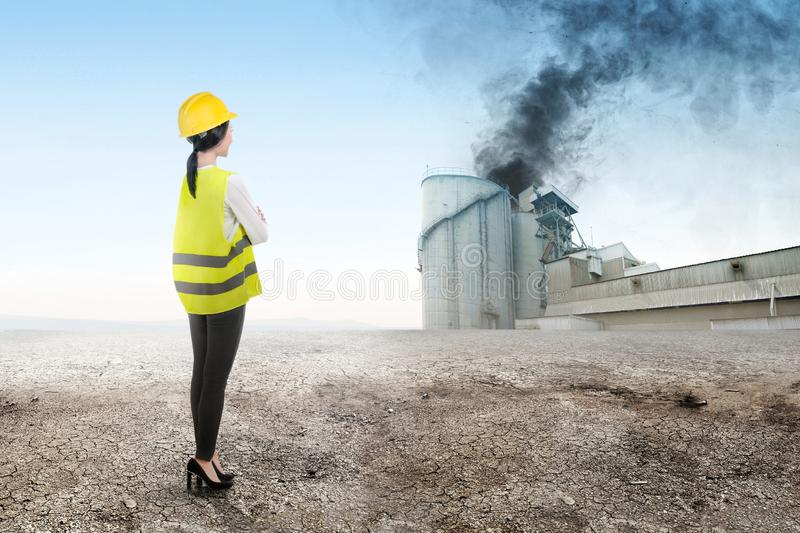 Rear view of Asian construction engineer woman looking at smoke and air pollution from the industrial factory stock photo